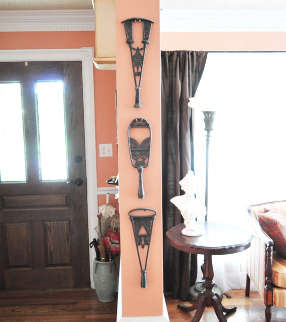 Art Nouveau lamp finials used as wall art in a narrow space