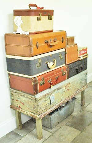 Stacked suitcases on a peeled and scraped painted box
