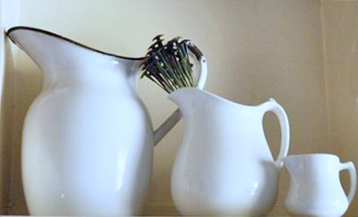 White, antique pitchers on a pantry shelf