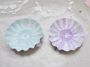 Painting metal flowers made from Christmas tree candle clips.