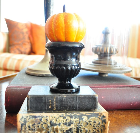 Fall decorating with a small pumpkin on top of black glass match holder
