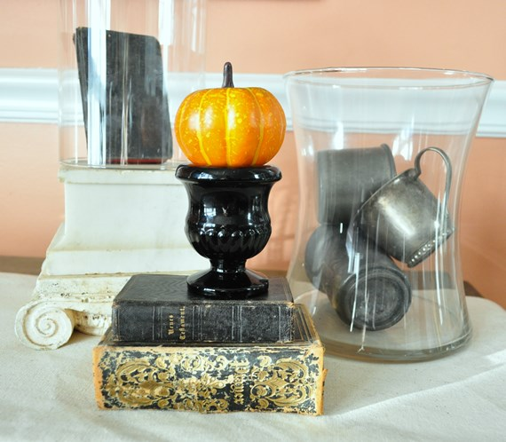 Tiny pumpkin on black glass match holder next to silver plate cups in a glass jar