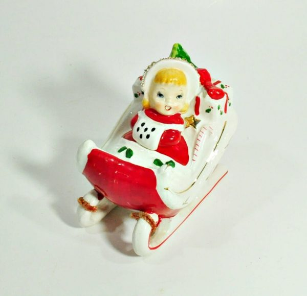 Vintage Christmas decoration of a little girl riding a sleigh filled with gifts, made by Relco