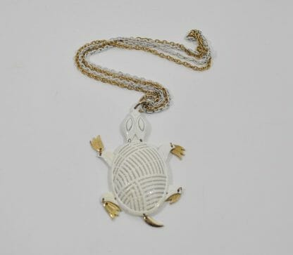 Vintage turtle necklace made by Alan in the 1970's. White and gold tone metal.