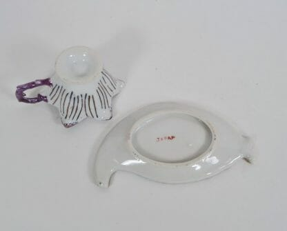 View of bottom of tiny leaf and flower cup and saucer