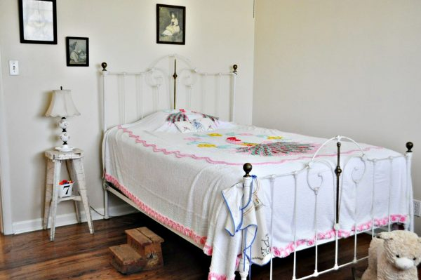 Guest bedroom, white iron bed, peacock, chenille bedspread, chippy white stool for bedside table.