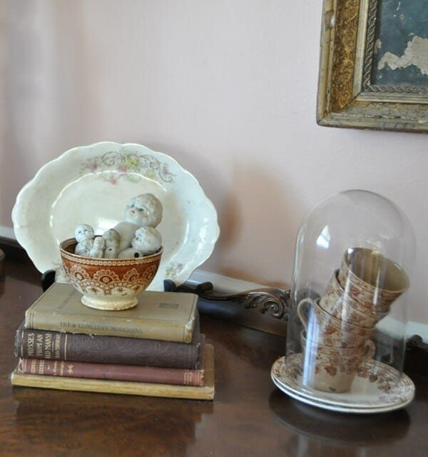 Close-up of buffet vignette with stacked, brown transferware cups under a cloche and armless, frozen Charlottes in a bowl.