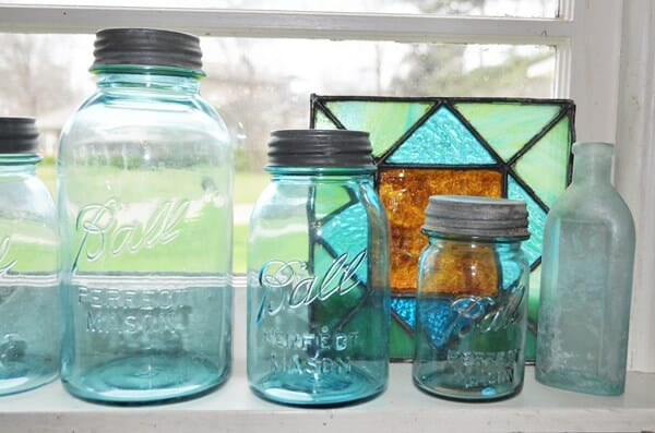 Blue canning jars in a kitchen window. The kitchen in the home tour of our old house.