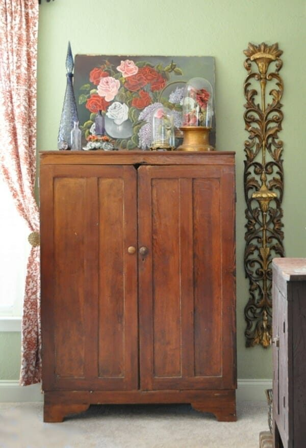 Primitive cabinet with a mix of mid century, florals, and fancy golds.