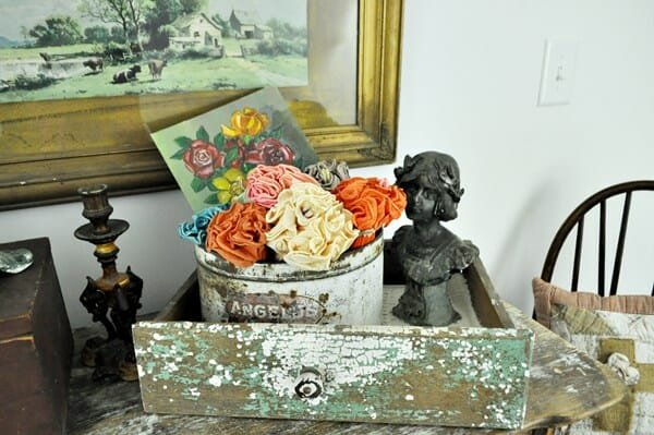 Chippy drawer, metal bust, floral painting and crepe paper flowers in an old, marshmallow can.