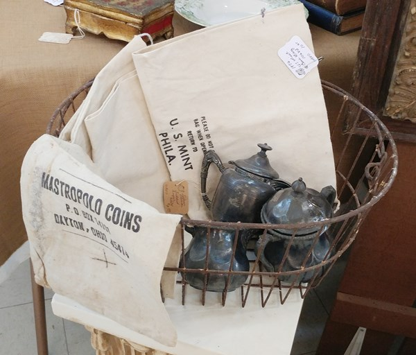 Vintage US Mint bags in a basket with silver plate creamer and sugars.