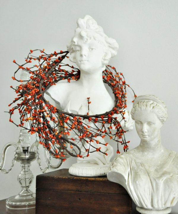 Bust with simple, fall, berry garland draped around her shoulders.