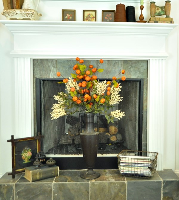 Fall arrangement on hearth in a tall, vintage, wooden, vase.