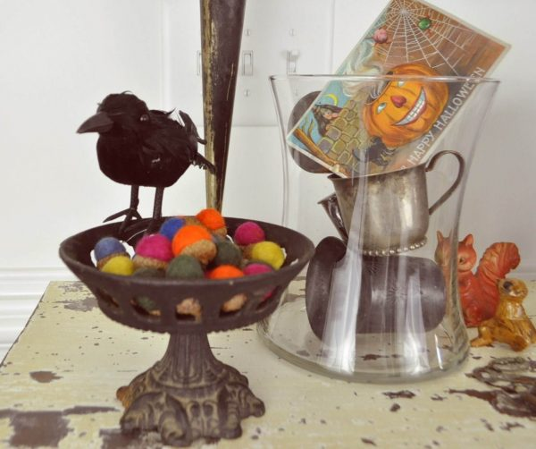 Felted acorns in a vintage iron bowl with a dollar store crow perched on top.
