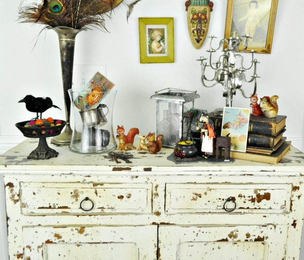 Fall and Halloween items on a chippy white chest