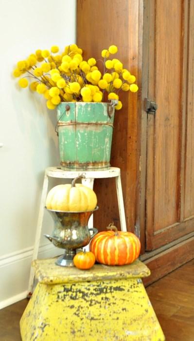 Fall arrangement using a yellow train step, taller stool, green, ice cream bucket, pumpkins, silver and yellow stems.